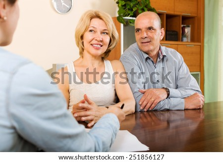 Smiling  mature couple discussing details of private insurance with agent - stock photo