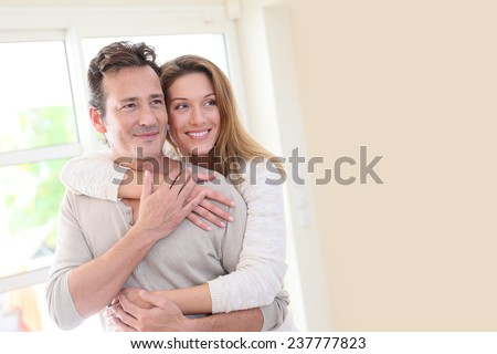 Smiling mature couple embracing each other at home - stock photo