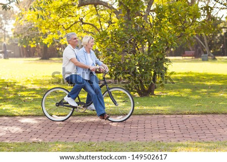 smiling mature couple enjoying bicycle ride at the park - stock photo