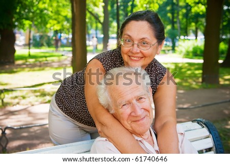 smiling mature couple enjoying fresh air in a park, they are different age, but they love each other - stock photo