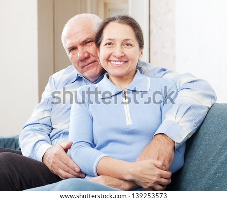 Smiling  mature couple sitting on sofa in home - stock photo