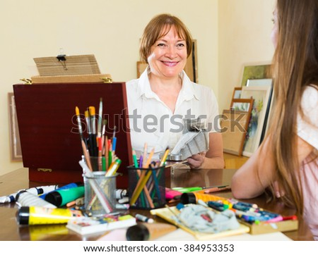Smiling mature female artist painting portrait of young girl at art studio - stock photo