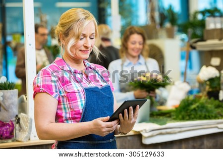 Smiling mature female florist using digital tablet with colleague working in background at shop - stock photo