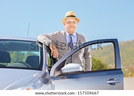 Smiling mature gentleman with hat posing next to his car on an open road - stock photo