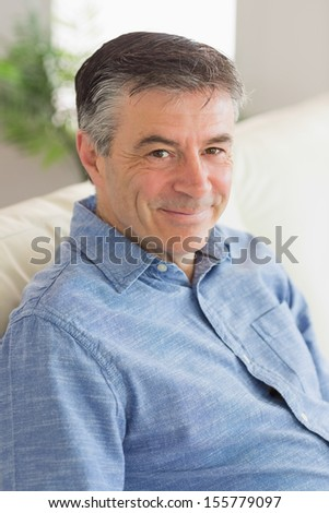 Smiling mature man sitting on a sofa in a living room - stock photo