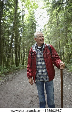 Smiling mature man walking in the forest path - stock photo