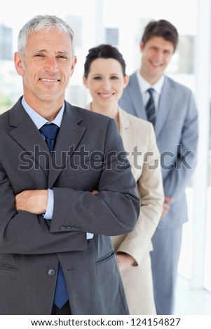 Smiling mature manager standing upright in front of his young business team - stock photo