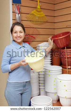 Smiling mature  woman chooses plastic flower pot in the store - stock photo