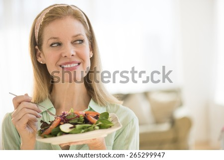 Smiling mature woman having salad while looking away at home - stock photo