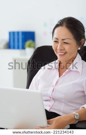 Smiling mature woman using laptop - stock photo
