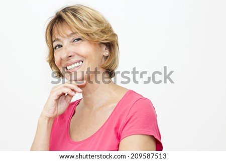 Smiling  mature woman with hand on her chin looking at camera. - stock photo