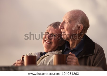 Smiling mature woman with husband in outdoors scene - stock photo