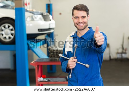Smiling mechanic looking at camera at the repair garage - stock photo