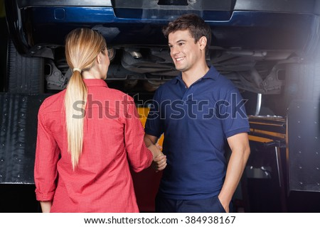 Smiling Mechanic Shaking Hand With Customer - stock photo
