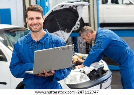 Smiling mechanic using a laptop at the repair garage - stock photo