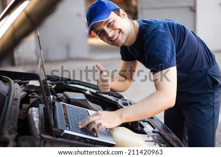 Smiling mechanic using a laptop computer to check a car engine - stock photo