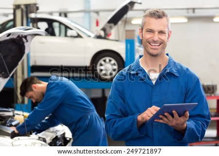 Smiling mechanic using a tablet pc at the repair garage - stock photo
