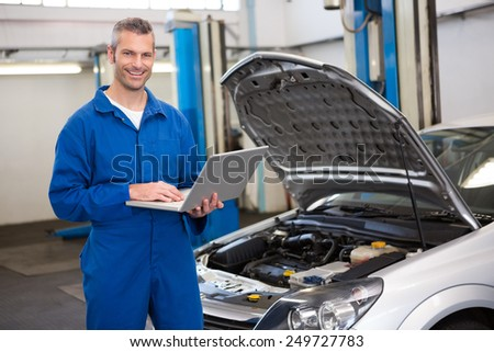 Smiling mechanic using his laptop at the repair garage - stock photo
