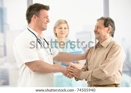 Smiling medical doctor shaking hands with happy senior patient, nurse in background.? - stock photo