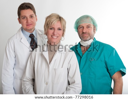 Smiling medical staff team with a surgeon a practitioner and a nurse - stock photo