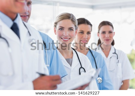 Smiling medical team in row in a hospital - stock photo