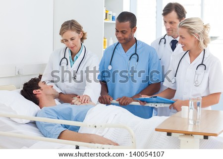 Smiling medical team talking to a patient - stock photo
