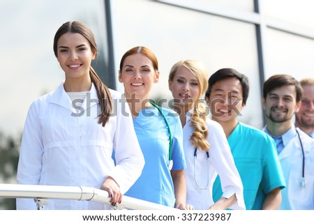 Smiling medics team standing in a row near the clinic - stock photo