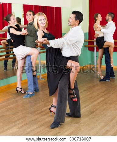 Smiling men and women enjoying of tango in class  - stock photo