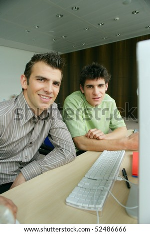 Smiling men in front of a laptop computer - stock photo