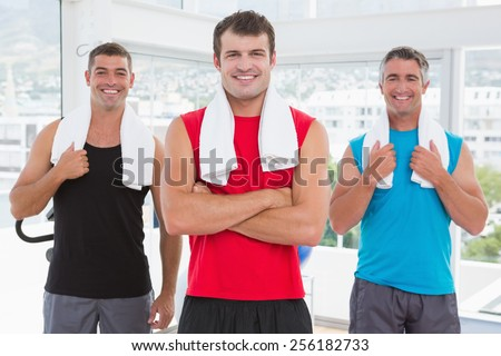 Smiling men looking at camera in fitness studio - stock photo