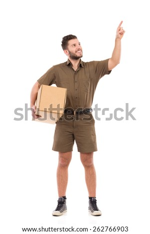Smiling messenger pointing up. Man in brown uniform holding package under his arm and pointing up. Full length studio shot isolated on white. - stock photo
