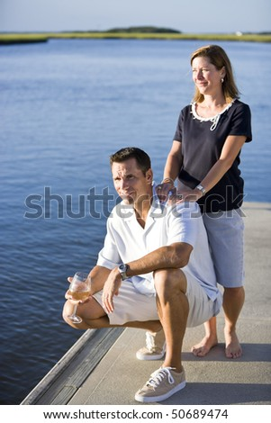 Smiling mid-adult couple relaxing with drink on dock by water - stock photo