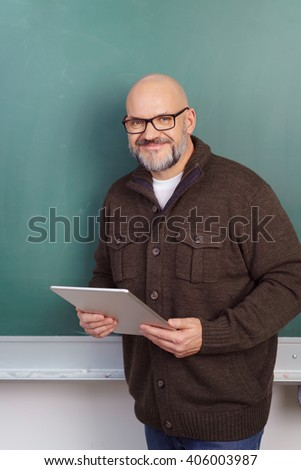 Smiling middle-aged balding male teacher or professor wearing glasses standing in front of a chalkboard holding a tablet in class - stock photo