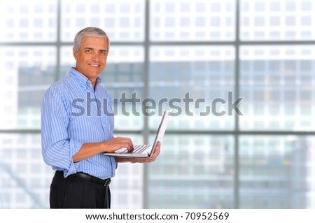 Smiling Middle Aged Businessman holding laptop computer with in front of large window in modern office. - stock photo