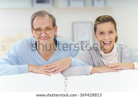 smiling middle aged couple leaning on their white sofa at home - stock photo
