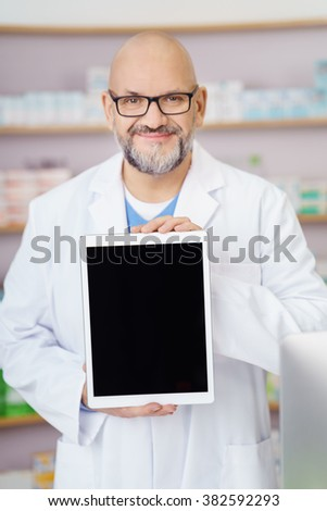 Smiling middle aged male pharmacist in a white lab coat standing in the pharmacy displaying a blank tablet screen towards the camera with a smile - stock photo
