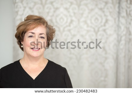 Smiling middle aged white woman with copy space on right. - stock photo