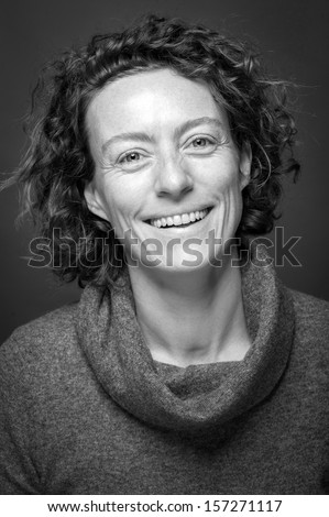 Smiling middle aged woman close up portrait. Black and white image. - stock photo