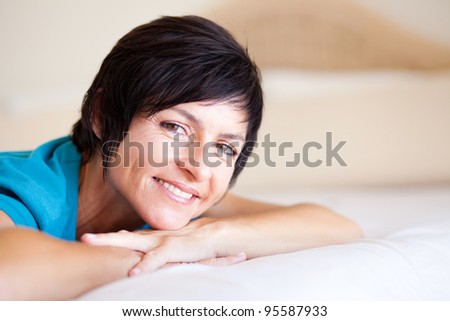 smiling middle aged woman lying on bed relaxing - stock photo