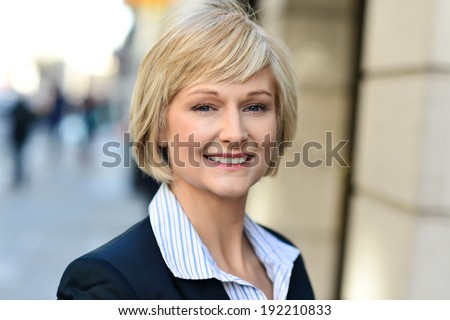 Smiling middle aged woman standing outside the office - stock photo