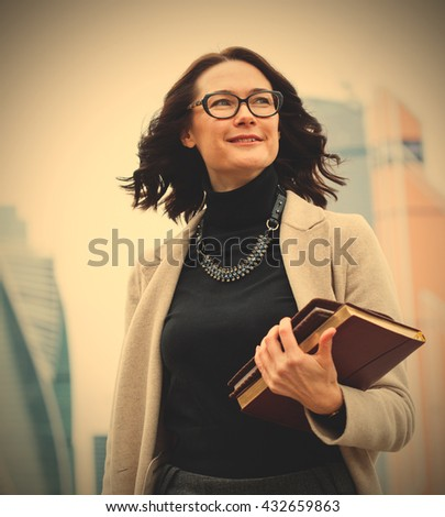 smiling middle-aged woman with glasses on his face, and with books in their hands on open air. instagram image filter retro style - stock photo