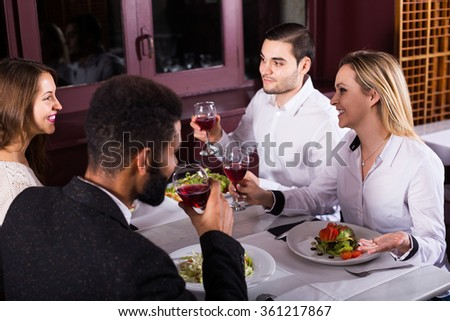 smiling middle class spanish people enjoying food in cafe and talking - stock photo