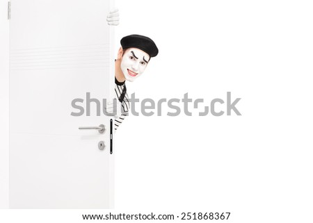 Smiling mime artist posing behind a wooden door isolated on white background - stock photo