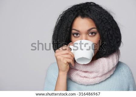 Smiling mixed race african american - caucasian girl wearing warm knitted sweater and scarf drinking hot drink from a cup with a biscuit, over gray background - stock photo