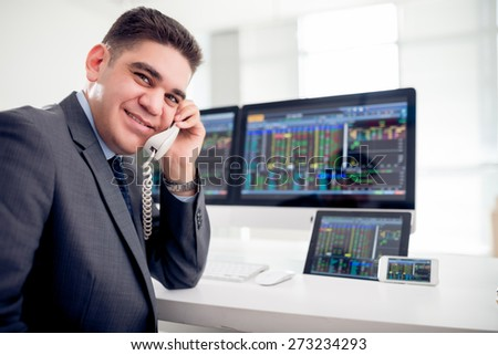 Smiling mixed-race businessman with financial data on computer screen, digital tablet and smartphone - stock photo