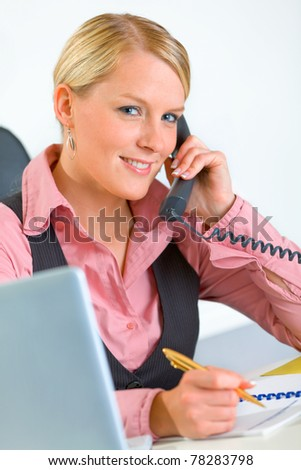 Smiling modern business woman sitting at office desk and talking on phone - stock photo
