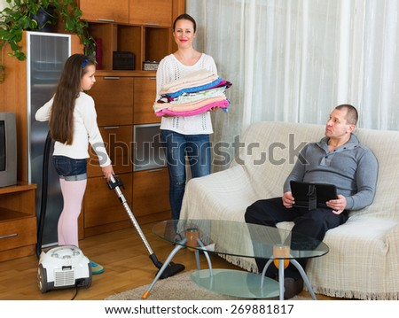 Smiling mom and cute girl doing general cleaning, man having rest. Focus on men - stock photo