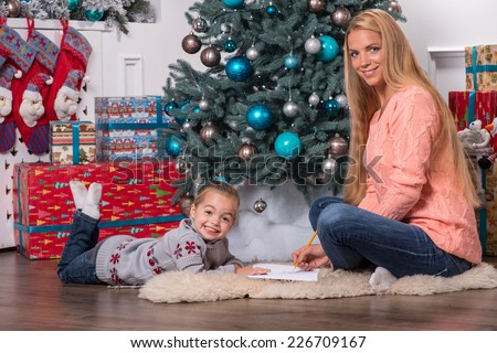 Smiling mom and daughter wearing nice warm sweaters and jeans sitting aside on the floor near the Christmas tree talking and writing a letter for Santa - stock photo