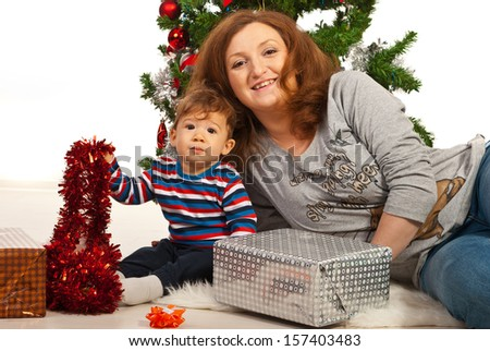 Smiling mother and baby sitting near Christmas tree - stock photo