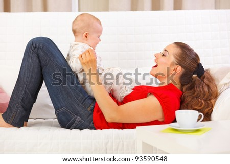 Smiling mother and cute baby playing on divan - stock photo